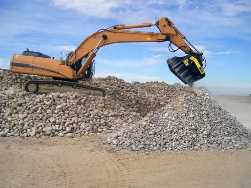 Caçamba Trituradora MB instalada em uma Escavadeira Hidráulica trabalhando com rochas.