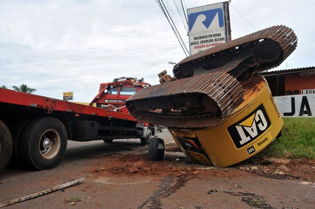 Escavadeira tombada após cair de caminhão prancha